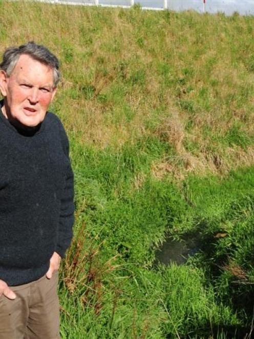 Blanket Bay resident Gerry Boyle stands beside a ditch where septic tank run-off has accumulated...
