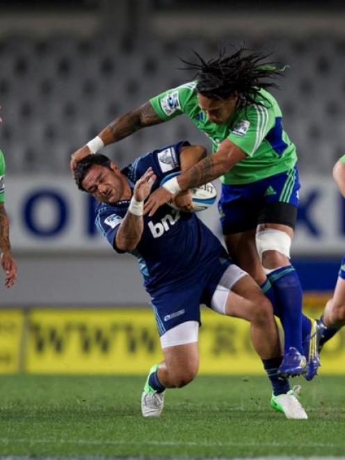 Blues halfback Piri Weepu is hit in an illegal tackle by Highlanders second five-eighth Ma'a Nonu...