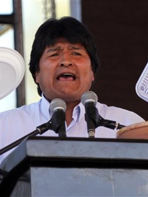 Bolivia's President Evo Morales holds up plates made of plastic as he speaks at the World People...