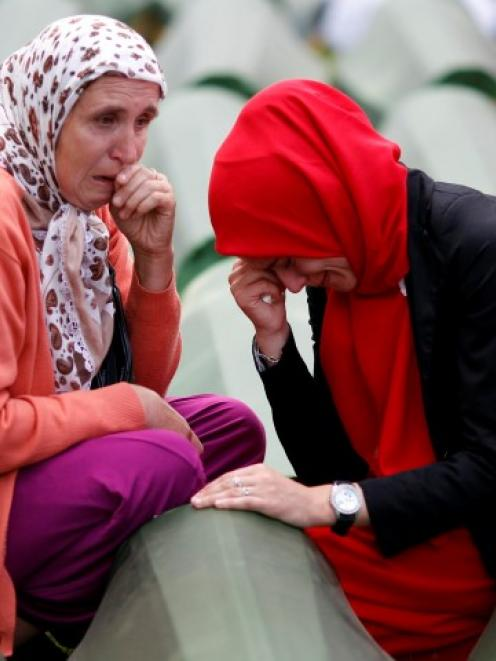 Bosnian Muslim women cry near the coffin of a relative, one of the 175 coffins of newly...