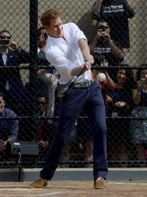 Britain's Prince Harry hits a baseball while participating in a baseball clinic in New York....