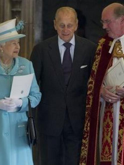 Britain's Queen Elizabeth II and her husband Prince Philip, centre, talk with the Dean of Windsor...