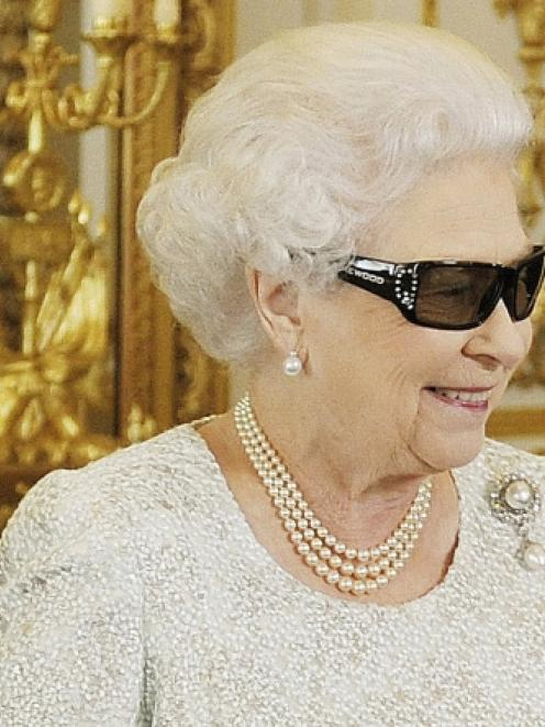 Britain's Queen Elizabeth watches a preview of her Christmas message with a pair of 3D glasses,...