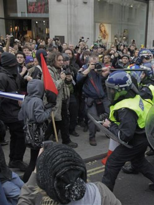 British riot police officers clash with demonstrators against the coalition government's spending...