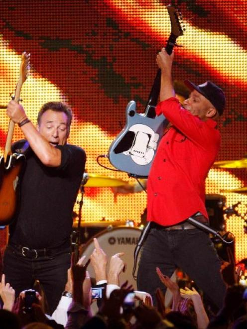 Bruce Springsteen (L) and Tom Morello perform 'Thunder Road' during the 2013 MusiCares Person of...