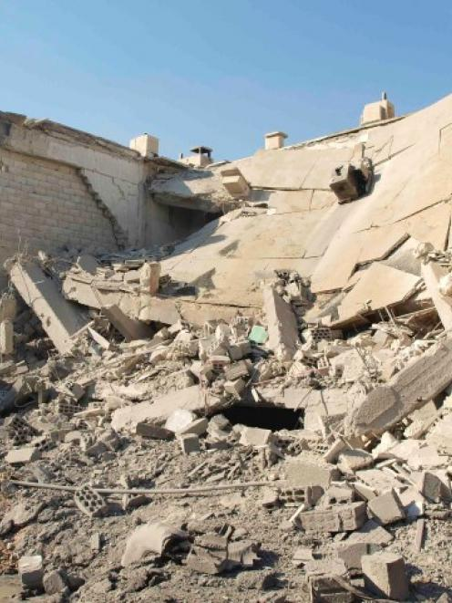 Buildings in Daria near Damascus show damage caused by missiles fired by a Syrian Air Force...