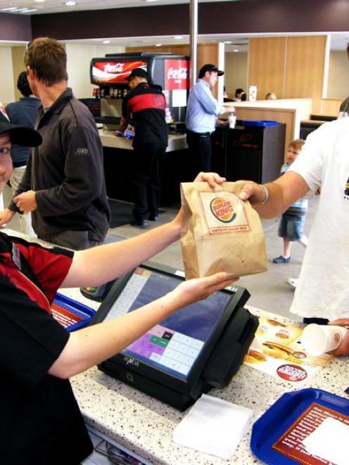 Burger King team member Louise Hanley serves Queenstown resident Josh Begley in the busy new...