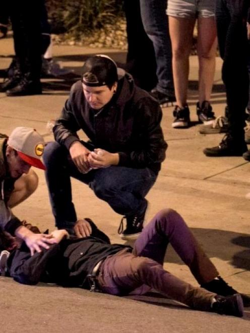 Bystanders tend to a man who was struck by a vehicle during the SXSW festival in downtown Austin...