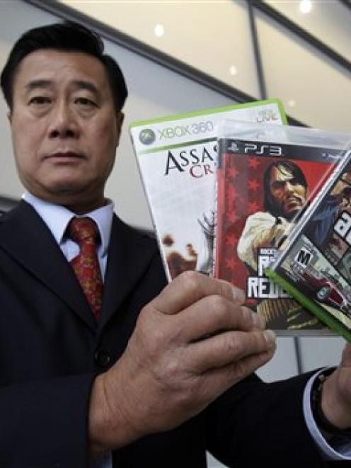 California State Senator Leland Yee, of San Francisco, holds up three video games after a news...