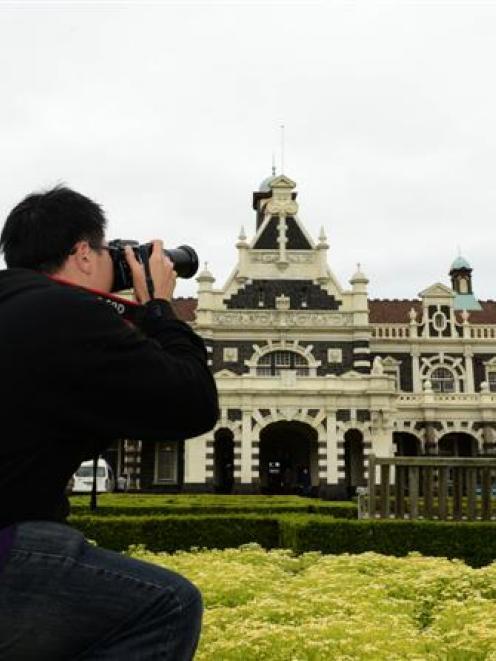 Canadian tourist Lennox Ruiz photographs the Dunedin Railway Station yesterday, after it was...