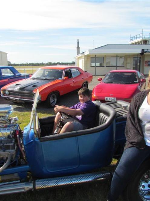 Car-lover Joel Klenner (10), in the driver's seat, and Whitestone Rodders club member Donna Boler...