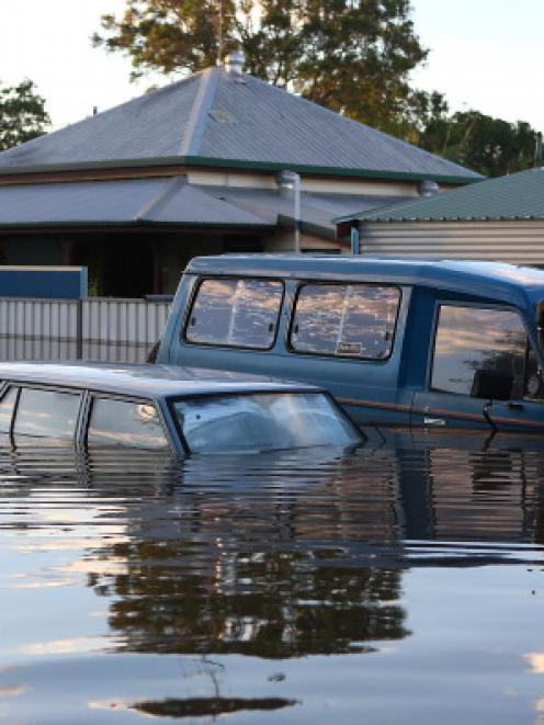 Cars float in a flooded street in Bundaberg.  (Photo by Chris Hyde/Getty Images)