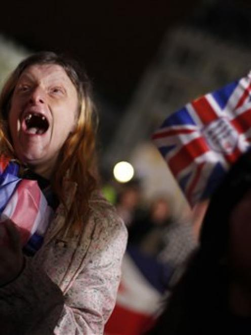 Caryll Foster, of Kingston on Thames, England, left, cheers with other royal enthusiasts as they...