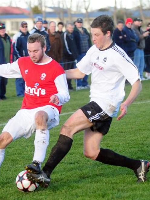 Caversham's Darren Overton (left) tangles with Roslyn-Wakari's Dave Shaw in the Chatham Cup match...
