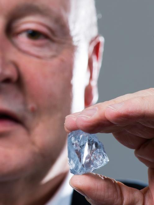 CEO Johan Dippenaar holding the exceptional 122.52 carat blue diamond recovered in June 2014....