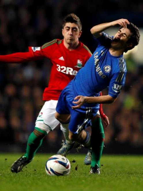 Chelsea's Oscar (front) is challenged by Swansea City's Pablo Hernandez during their English...