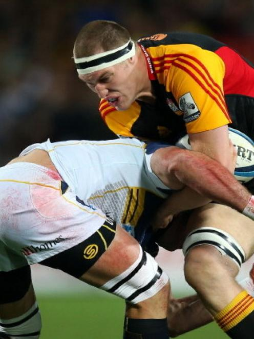 Chiefs lock Brodie Retallick tries to break the tackle of a Brumbies defender during the Super...