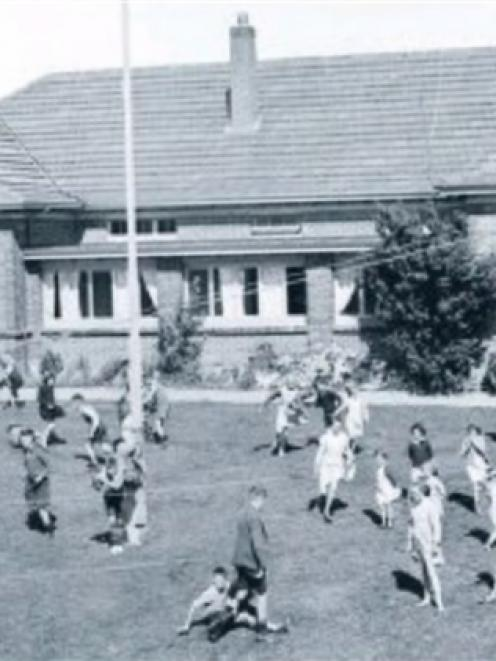 Children at play outside one of the three Glendining cottages in Andersons Bay in November 1950.