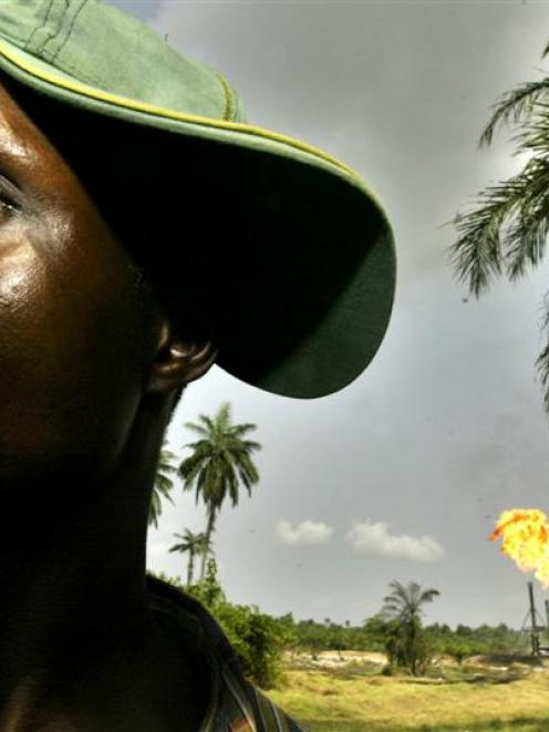 Chinedu Ugoma stands near a gas flare belonging to the Agip Oil company in Idu Ogba in Nigeria's...