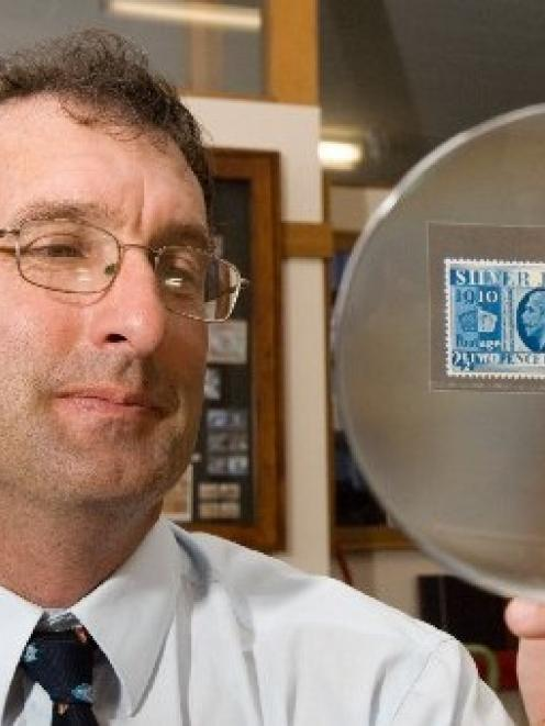 Christopher Burtt, of stamp auctioneer John Mowbray International, handles a 1935 silver jubilee...
