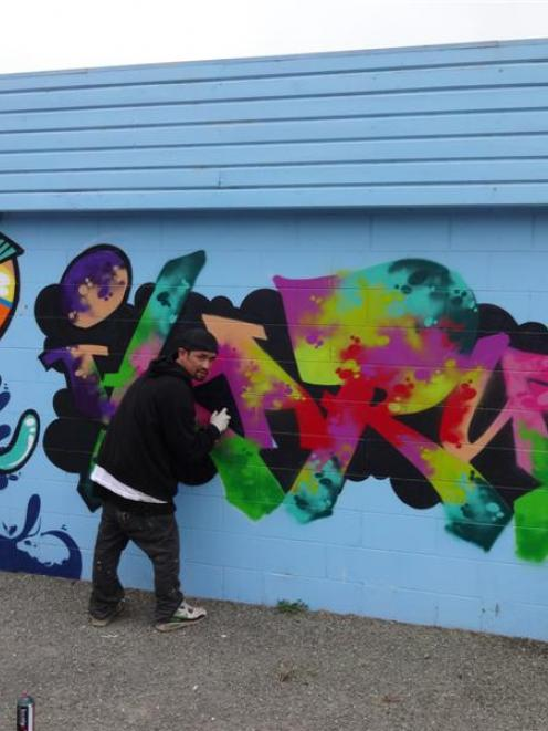 Christchurch graffiti artist Nick 'Icarus' Tam works on his 'fish and chips  graffiti' at the...