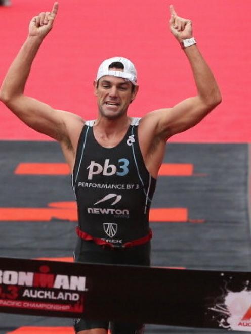 Christian Kemp of Australia celebrates winning the Ironman 70.3 Auckland triathlon today. (Photo...