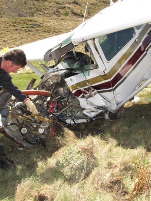 Civil Aviation Authority safety investigator Colin Grounsell  examines  the wreckage of the...