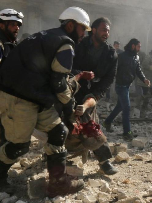 Civil defence members carry a wounded man at a site hit by what activists said were explosive...