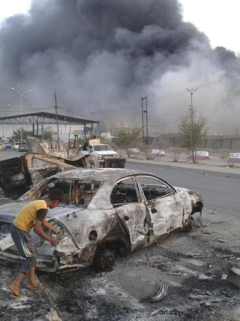 Civilian children stand next to a burnt vehicle during clashes between Iraqi security forces and...