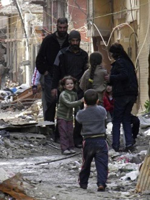 Civilians stand along a street amid garbage and rubble of damaged buildings in the besieged area...