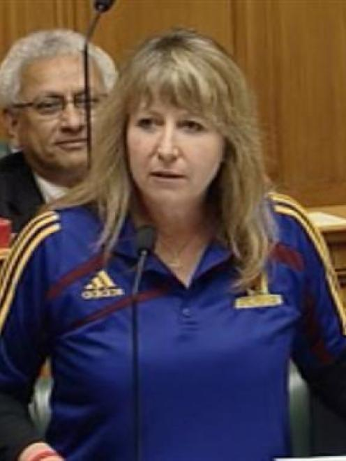 Clare Curran, wearing a Highlanders jersey, stands in Parliament yesterday. Photo by TVNZ.