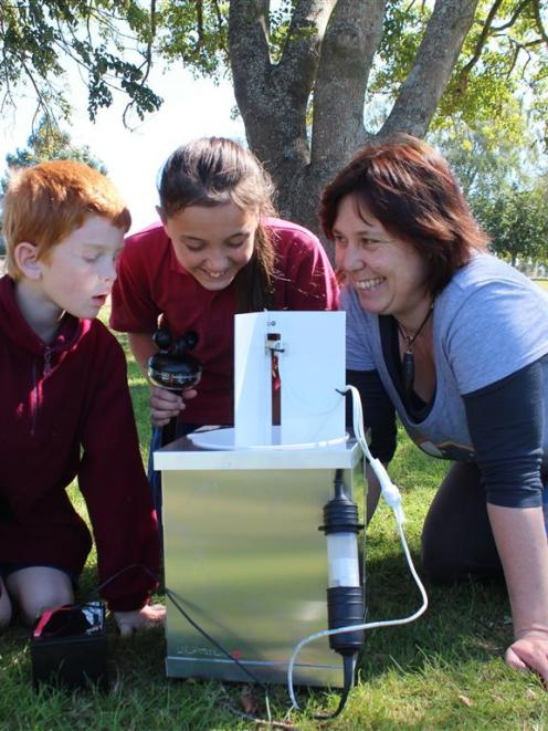 Clutha Valley School pupils Nathan Bocock (8) and Vera Stirling (12) check moth traps under the...