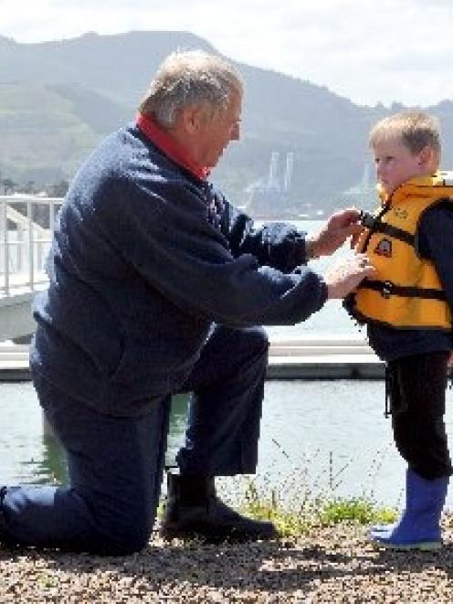 Coastguard Dunedin president Lox Kellas, of Portobello, prepares Harwood youngster Harper Wilson ...