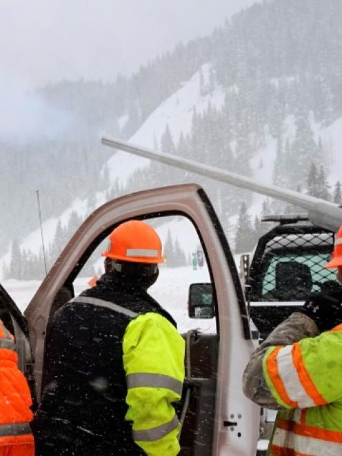 Colorado Department of Transportation (CDOT) workers watch a shell fly out of a truck-mounted ...