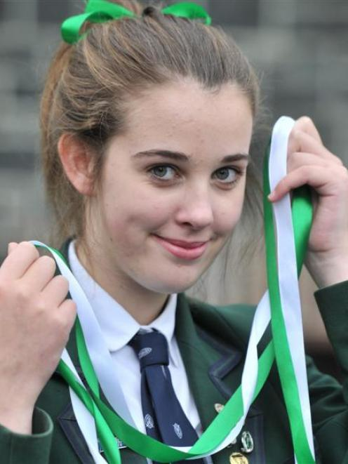 Columba College pupil Caitlin Addison (17) with green and white ribbons which will be worn by...
