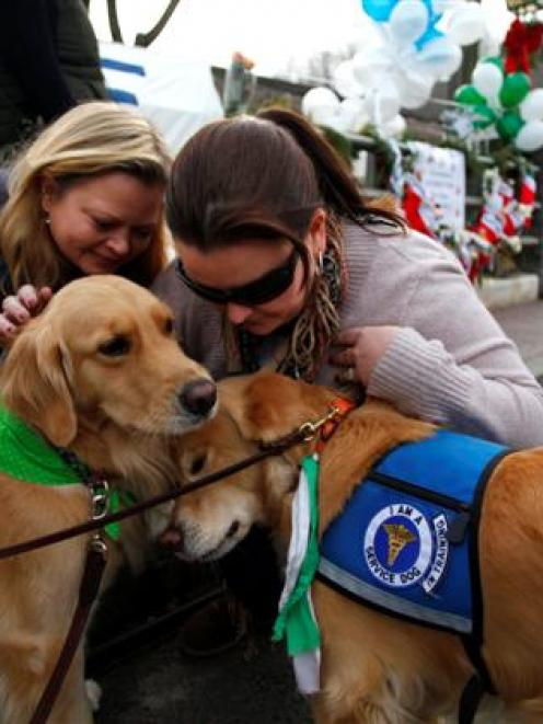 Comfort dogs receive attention from two women near a memorial for the Sandy Hook Elementary...