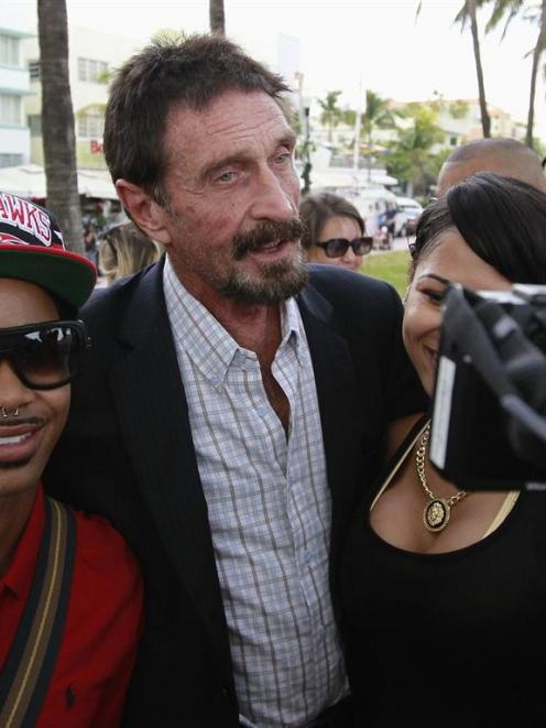 Computer software pioneer John McAfee poses with tourists as he speaks with reporters outside his...