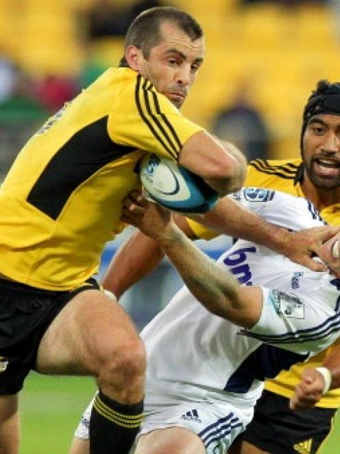 Conrad Smith fends Chris Noakes of the Blues during the round two Super Rugby match between the...