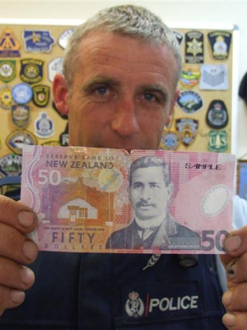 Constable Greg Nolet holds a counterfeit $50 note presented at a Wanaka shop this week. Photo by...