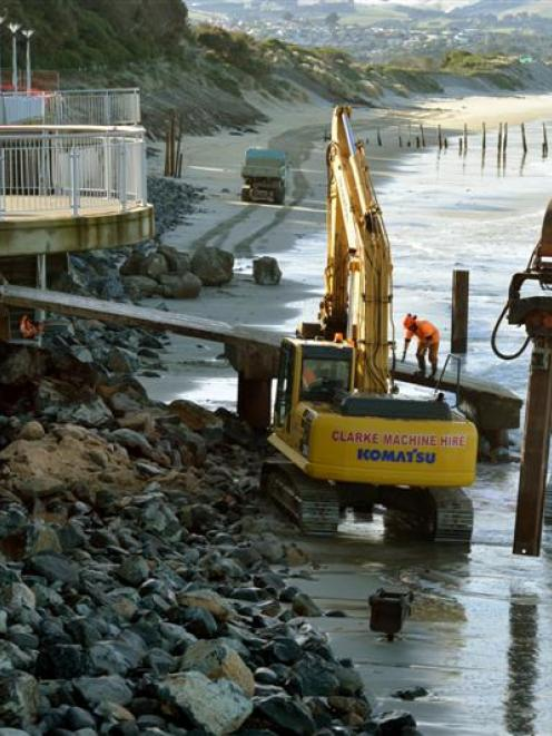 Contractors take advantage of low tide yesterday to continue piling rocks against the bottom of...