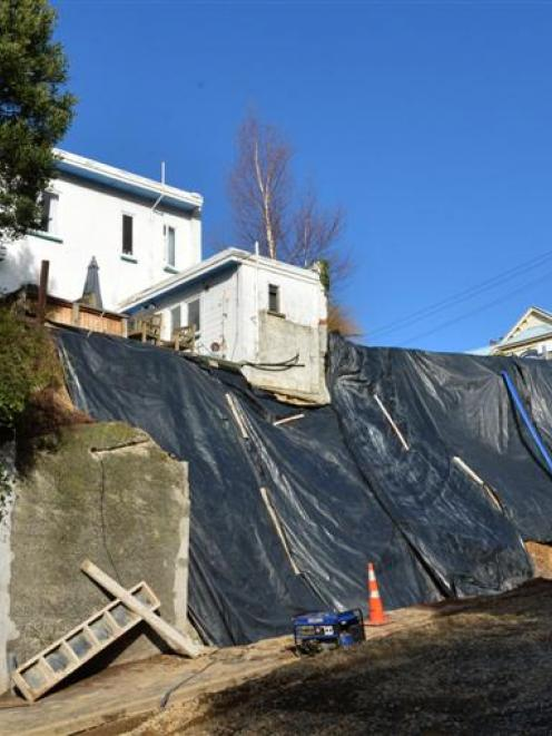 Contractors work to build a retaining wall after flooding last year brought down a 100-year-old...
