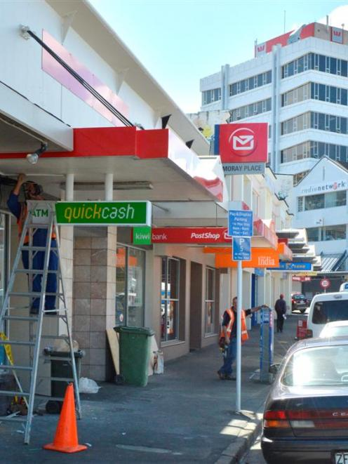 Contractors work to finish the new New Zealand PostShop in Moray Pl, in Dunedin, in time for...