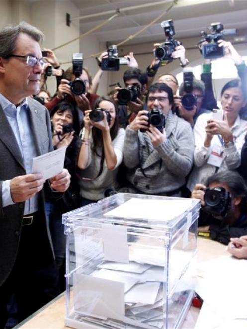 Convergencia i Unio (CIU) party's candidate Artur Mas is surrounded by photographers before...