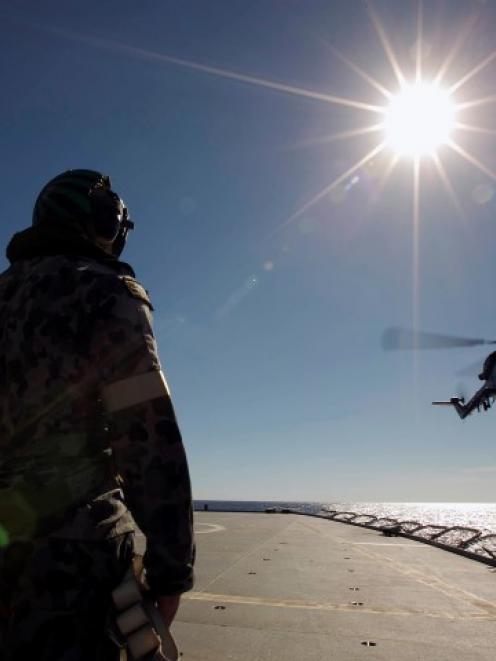 Crew aboard the Australian Navy ship HMAS Success watch as a helicopter participates in a...