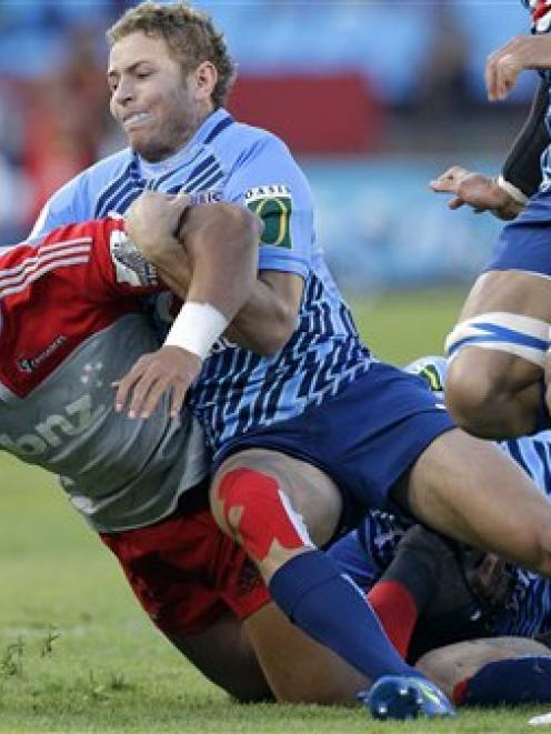 Crusaders back Robbie Fruean, left, is tackled by Johann Sadie. (AP Photo/Themba Hadebe)