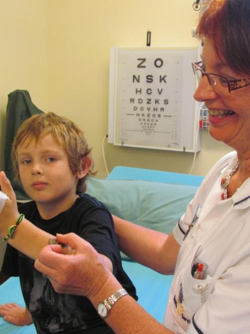 Cullen Park (8) gets medical attention from Oamaru registered nurse Glynis Kappely, right, after...