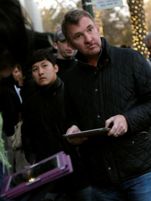 Customers wait in line for the initial sales of the iPad mini at Apple's retail store in Palo...