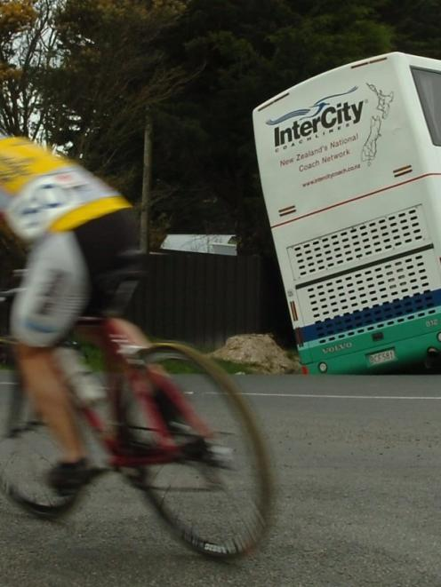 Cyclists competing in the Otago junior cycling championships pass an Intercity bus which slipped...