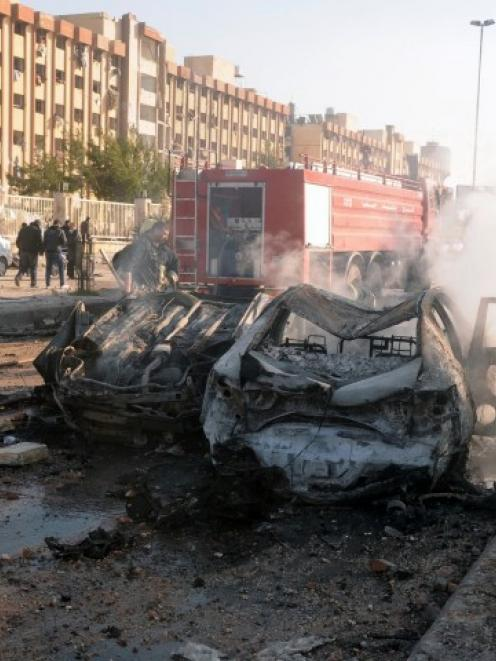 Damaged cars are seen at the site where two explosions rocked the University of Aleppo, killing...
