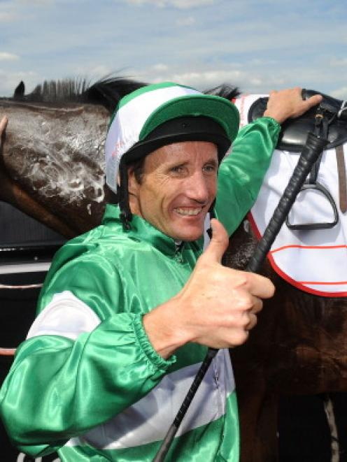 Damien Oliver celebrates winning the AAMI Victoria Derby riding Fiveandahalfstar during Victorian...